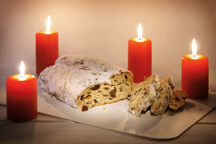Stollen amidst candles in plate on table