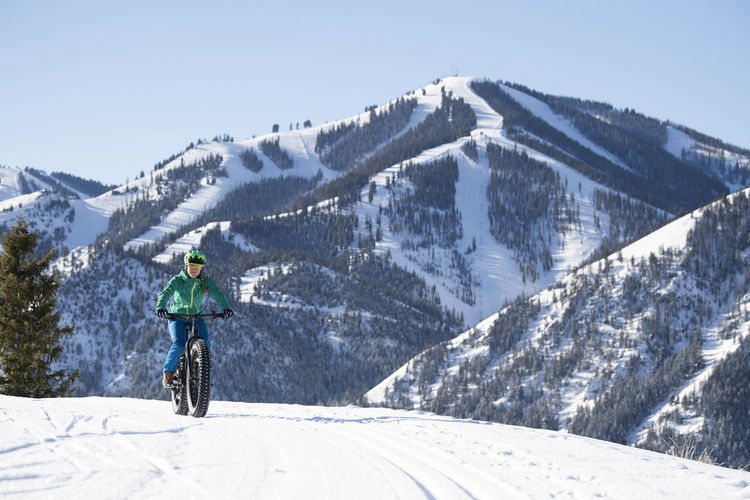 Man riding motorcycle on snowcapped mountains against sky