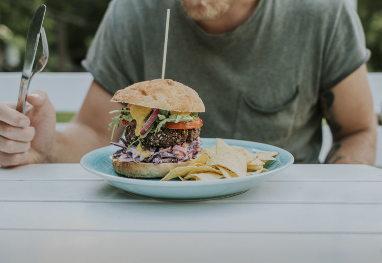 Midsection of man eating burger and potato chips while sitting at table in yard