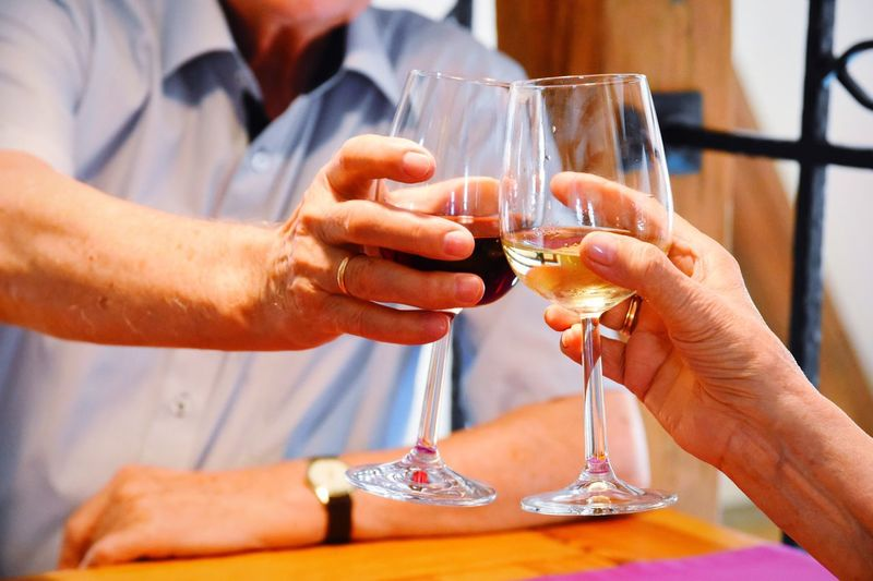 Midsection of man toasting wine woman while sitting at table