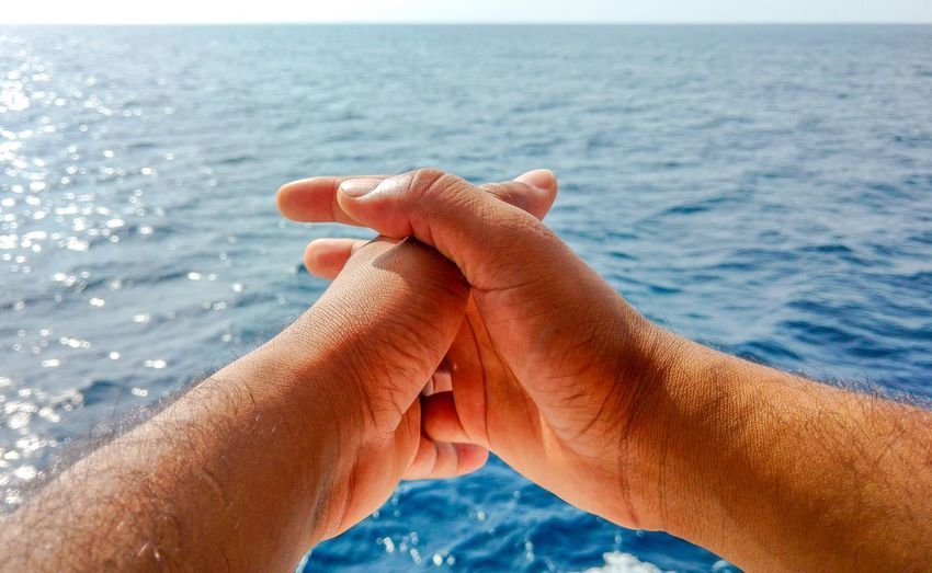 Close-up of man hands with sea in background. man in a thinking position