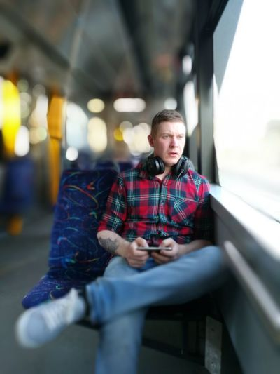 Handsome Man Sitting In Bus With Mobile Phone And Headphones Looking Away