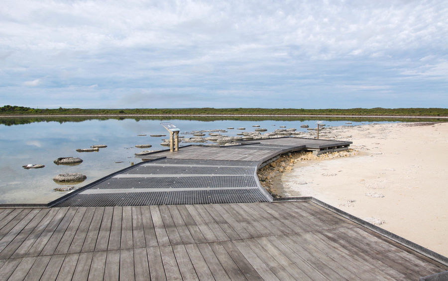 Observation point and walkway at Lake Thetis with stromatolites and sandy beach in Western Australia. Australia Beach Cluster Coastal Fossil Geology Lake Lake Thetis Landscape Layered Living Marine Nature Observation Point Rare Saline Lake Sand Sediment Stromatolites Thetis Thrombolites Viewing Platform Walkway Waterfront Western Australia