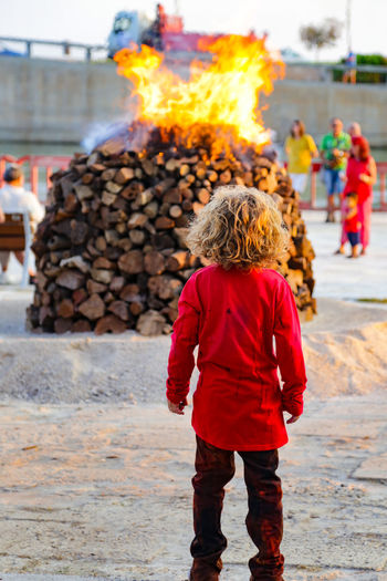 Pile Of Wood Spanish Building Exterior Burning Child Childhood Curiosity Day Fire Flame Full Frame Heat - Temperature Kid Leisure Activity Lifestyles One Person Outdoors People Pile Real People Rear View Spanish Culture Standing Traditional Festival Wood - Material