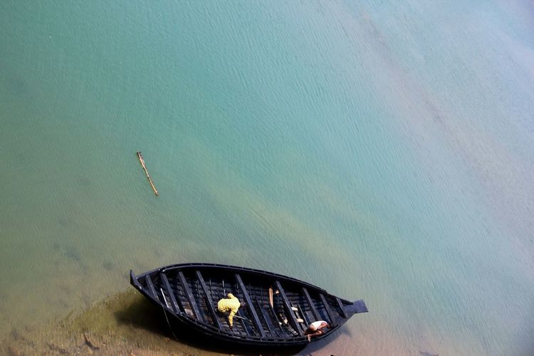 High angle view of fishermen in boat moored at shore