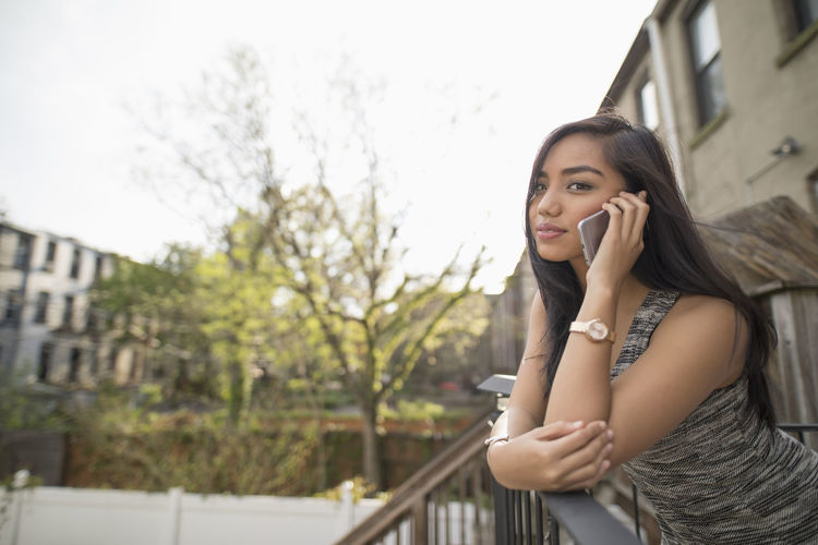 Portrait of young woman using mobile phone against clear sky