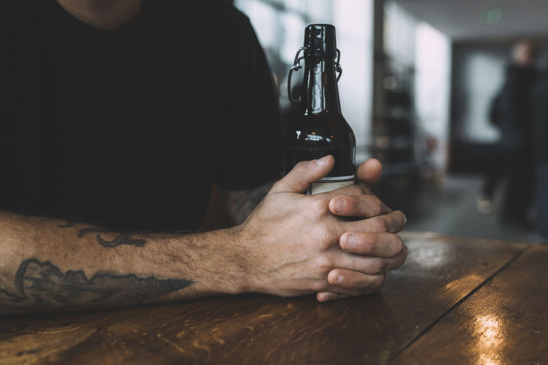 Close-Up Of Man Holding Beer Bottle