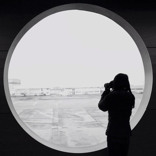 Woman Photographing From Circular Window At Airport
