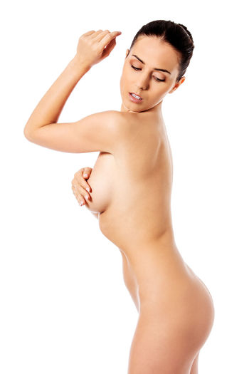 Naked young woman posing while standing against white background