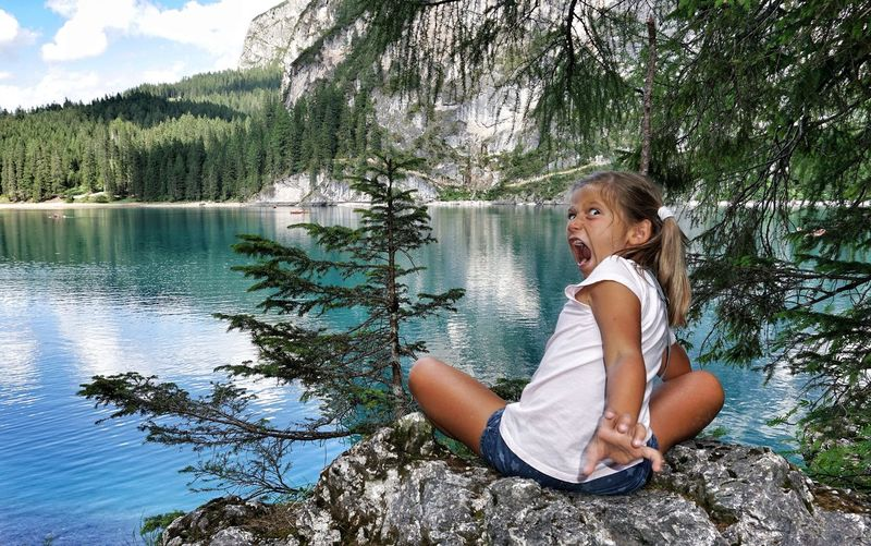 Portrait of mischievous girl sitting on rock at forest