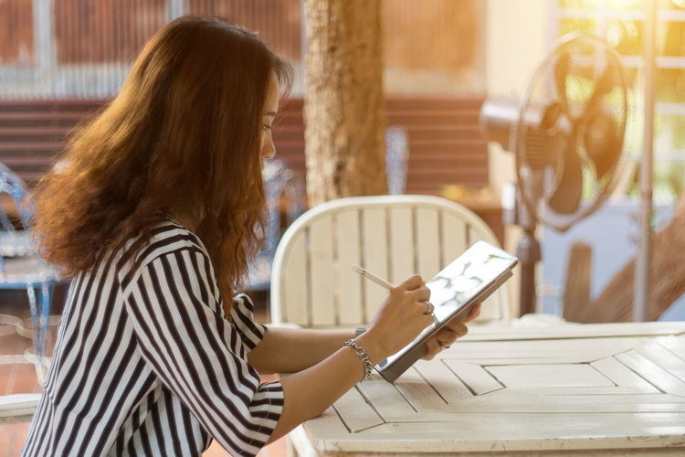 Side view of businesswoman using digital tablet at table