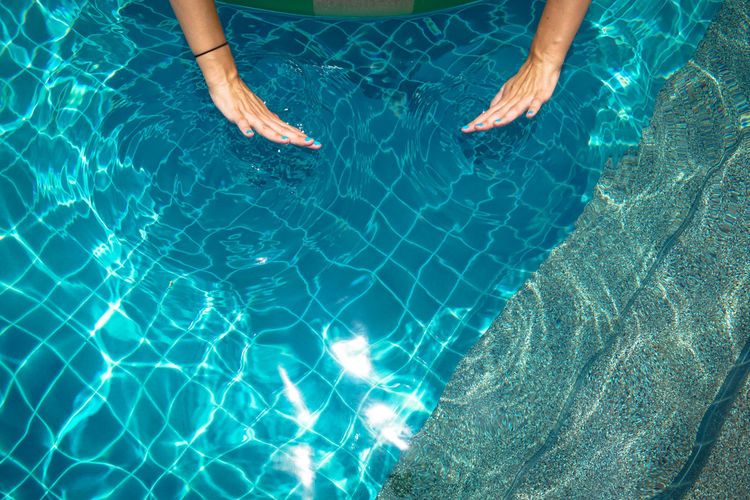 Cropped Hands Of Woman Swimming In Pool
