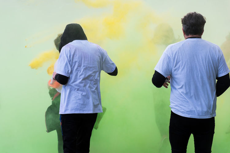 Rear view of man and woman standing amidst powder paint
