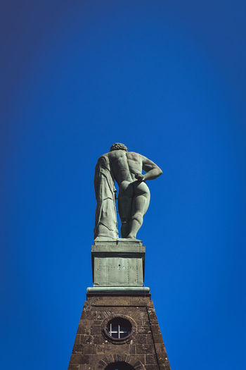 The Hercules monument in Kassel Art is Everywhere Clear Sky Copper Art Hercules Kassel Bergpark Schloss Wilhelmshöhe Statue Architecture Art Behind Building Copper  Creativity Day Human Representation Landmark Low Angle View Male Likeness Monument No People Sky Background