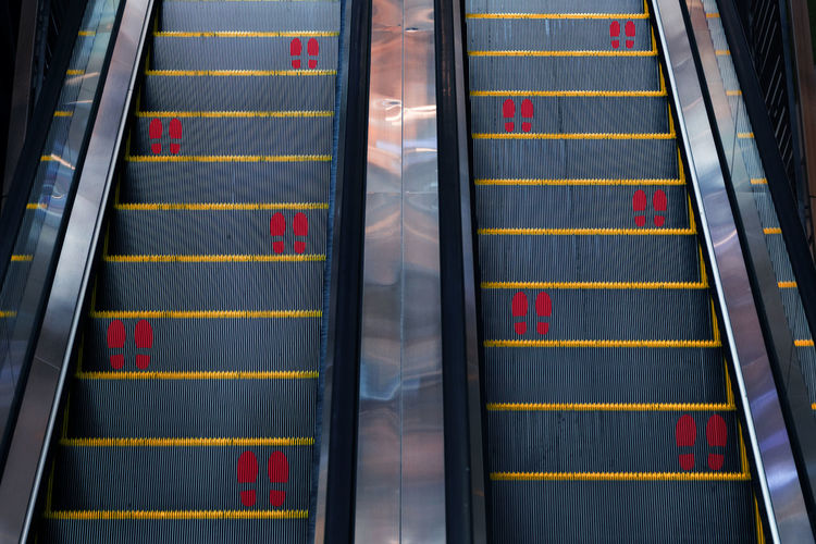 Sticker foot print social distancing symbol on escalator new normal covid-19 coronavirus pandemic