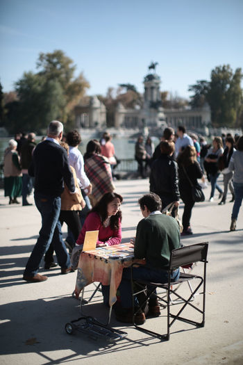 A fortune teller in the Retiro Park in Madrid, Spain Crowd Focus On Foreground Fortuneteller Lifestyles Park Retiro Sitting Spain, Madrid, Tourism, Tourist, Buildings Women