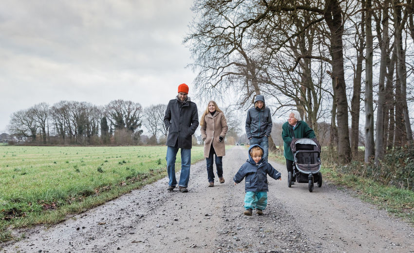Family walking on dirt road during winter