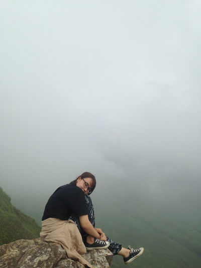 Portrait of woman sitting on cliff during foggy weather