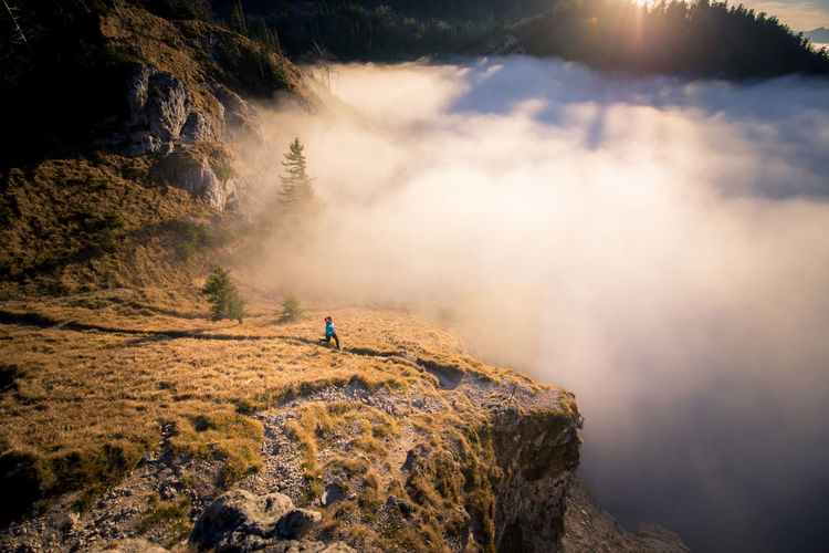 Woman jogging on mountain in foggy weather