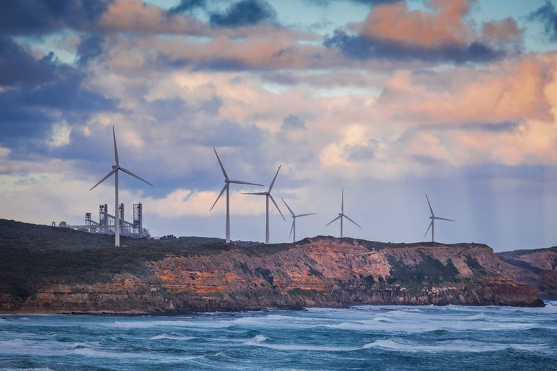 Windmills on cliff by sea against sky
