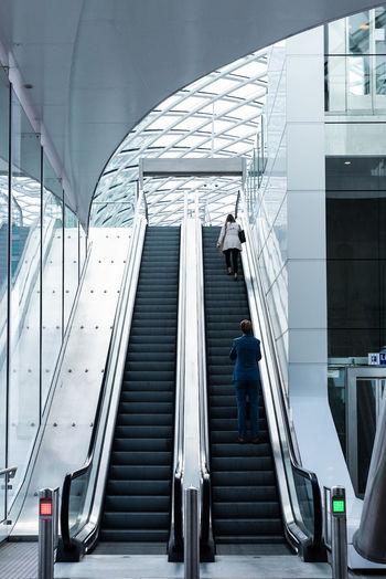 Rear view of man walking on escalator