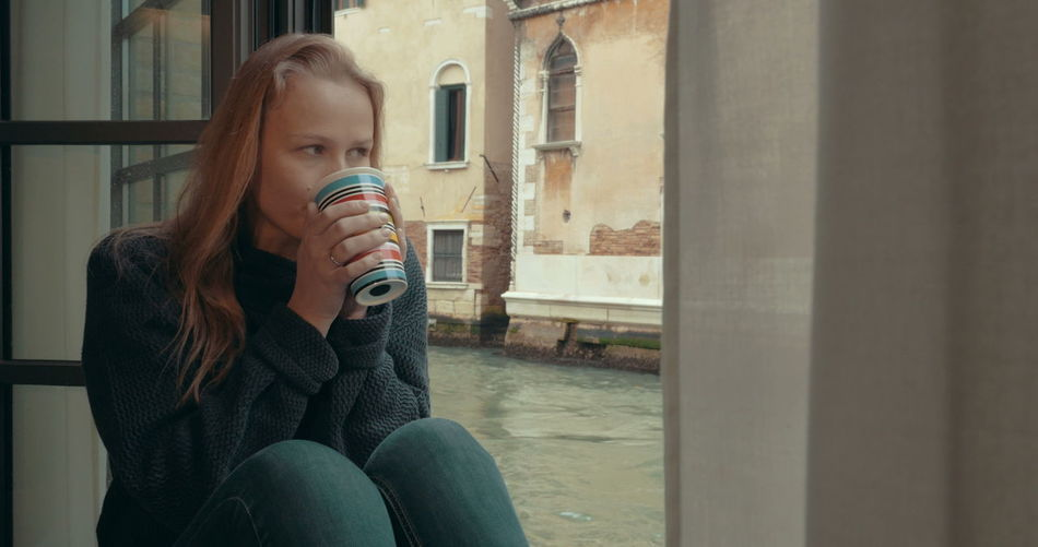 Midsection of woman drinking coffee in glass window