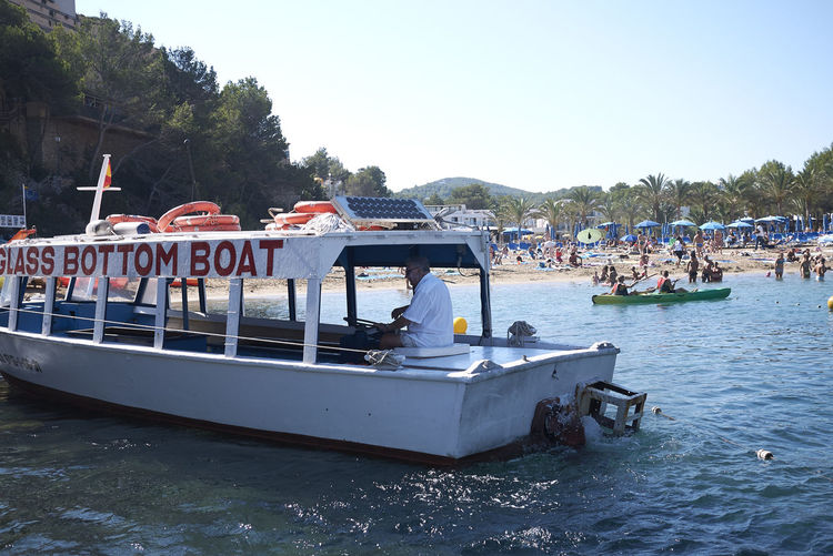 Tour boat of Cala Salada Ibiza Europe Spaın Balearic Islands Cala Salada Holiday Vacations Tourism Touristic Nautical Vessel Water Mode Of Transportation Transportation Sky Group Of People Tree Travel Real People Sea Flag Crowd Outdoors Tour Boat Glass Bottom Boat