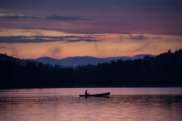 Silhouette person in boat on lake against sky during sunset