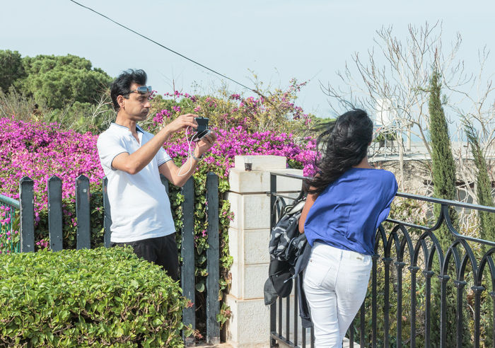 Haifa, Israel, November 19, 2016: Young boy photographing a young girl on his mobile phone in Haifa, Israel Adults Only Boy Camera Couple Day Flower Fun Girl Happy Man Mid Adult Mid Adult Men Mid Adult Women Mobile Outdoors People Phone Photo Smiling Smiling Face Summer Taking Photos Togetherness Woman Young