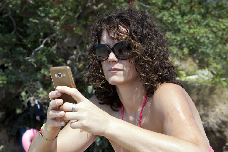 Woman using mobile phone during sunny day