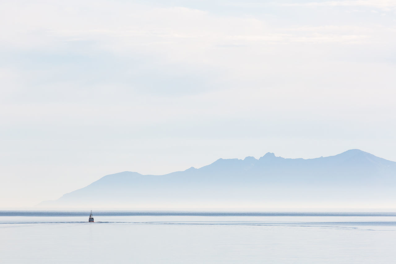 Seascape with mountain range in background