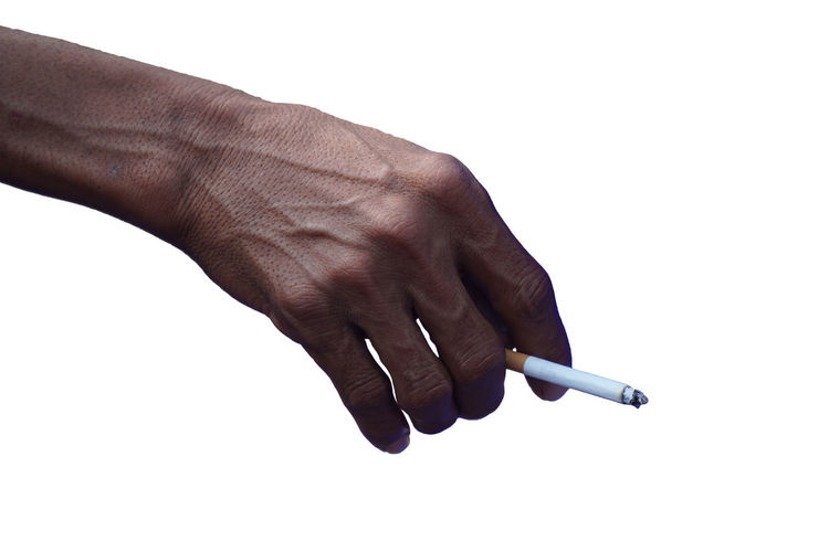 Close-up of hand holding cigarette against white background