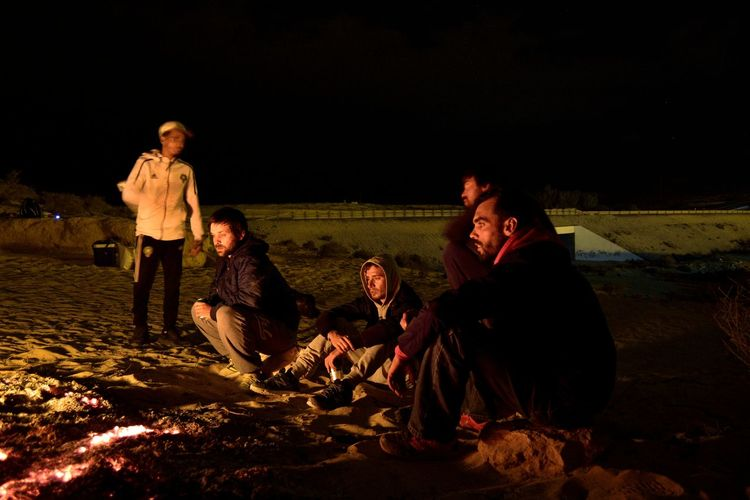 People sitting on land at night