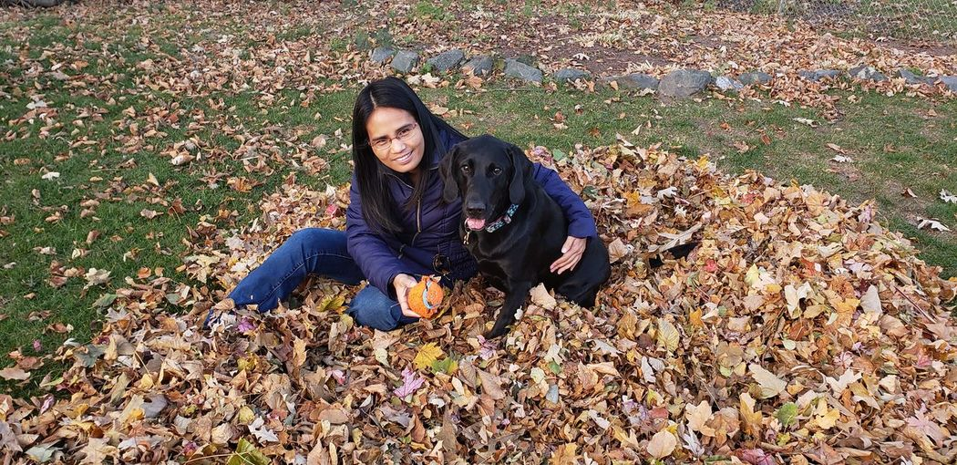Portrait of woman sitting with dog on fallen autumn leaves at park