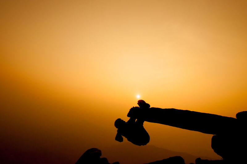 Silhouette Person Climbing On Cliff Against Sky During Sunset