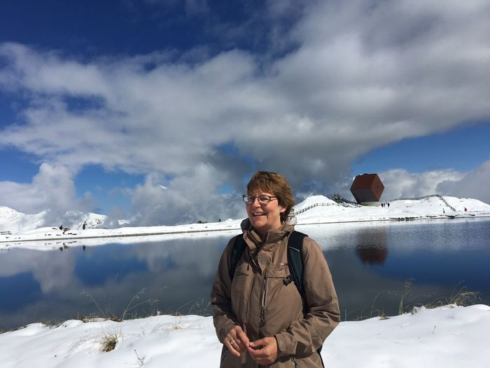 Smiling mature woman standing on snow against lake