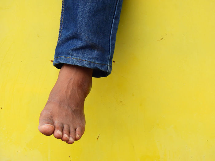 Bare Foot Human Body Man Minimalist Wall barefoot Body Part Finger Hanging Legs Human Human Body Part Human Foot Human Leg Human Legs Jean Jeans Lifestyles Male Men Minimalism One Person Yellow Yellow Background Yellow Wall
