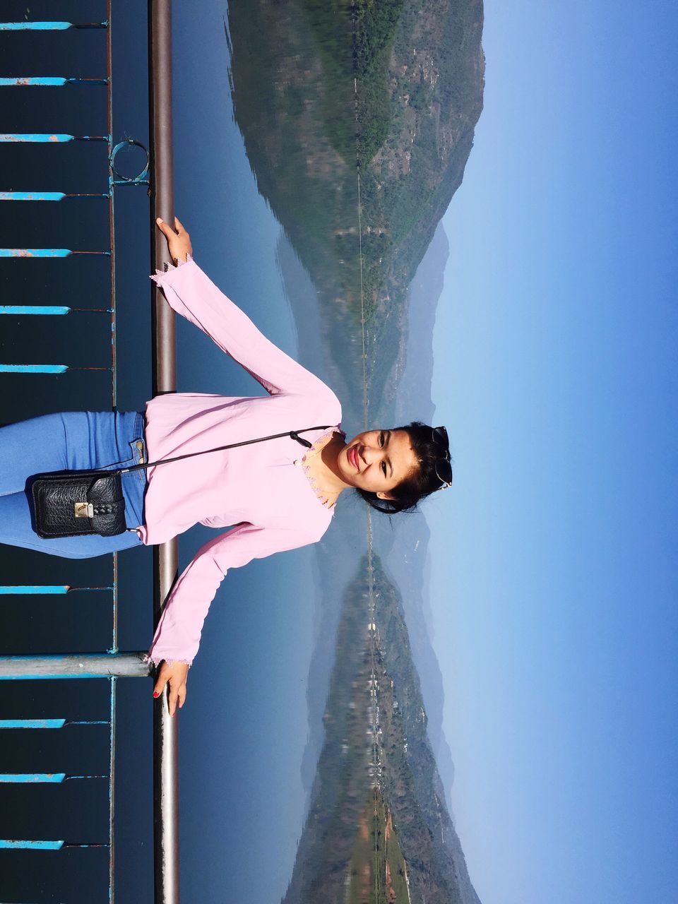 Portrait Of Smiling Woman Standing On Bridge Against Clear Sky
