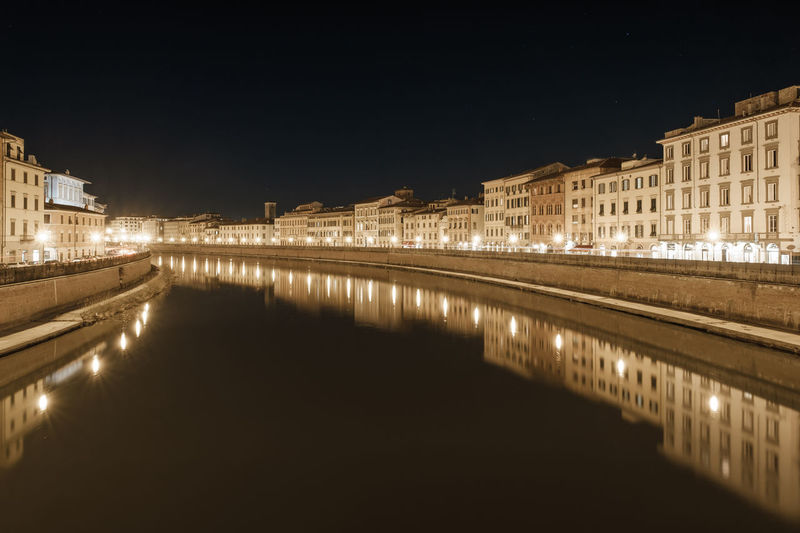 Reflection of illuminated buildings in river against sky at night
