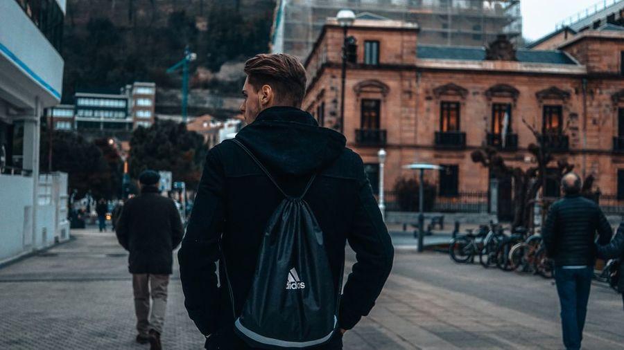 Rear view of man walking on zebra crossing in city