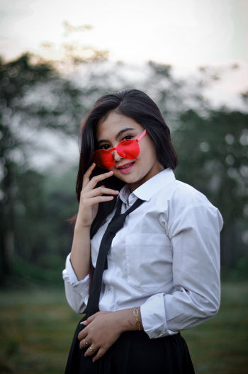 Portrait of young woman wearing shirt and tie