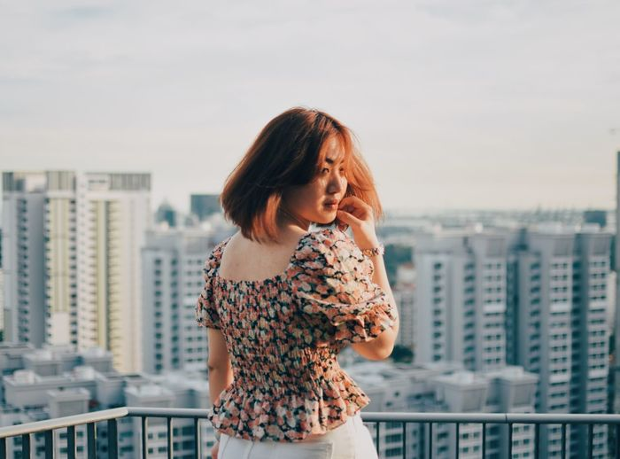 Beautiful young woman standing against buildings in city against sky