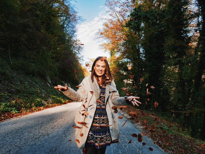 Portrait of smiling young woman on road against trees