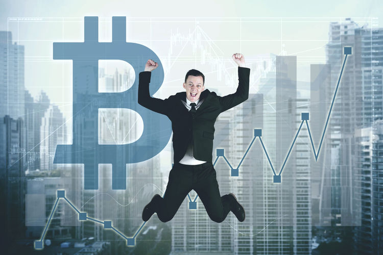 Digital composite image of businessman jumping against bitcoin symbol and city