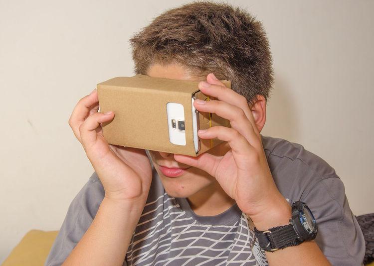 Close-up of boy looking in smart phone through cardboard virtual reality simulator