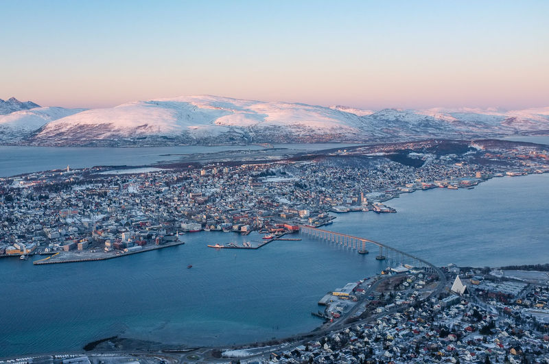View of Tromso in Norway in the Arctic Circle with mountains in the background Tromsø Aerial View Architecture Blue Bridge Bridge - Man Made Structure City Cityscape Cold Temperature Landscape Mountain Mountain Range Nature No People Outdoors Scenics Sea Sky Snow Snowcapped Mountain Sunset Town Travel Destinations Water Winter