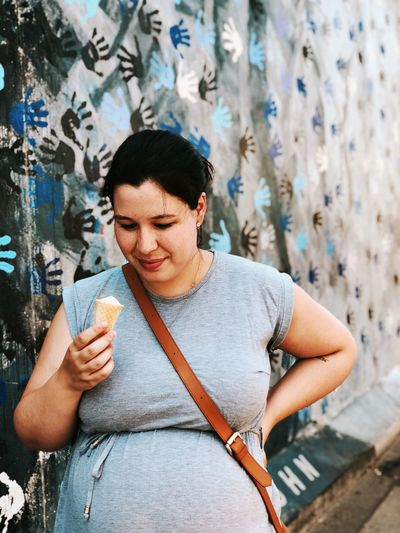 Pregnant woman having ice cream cone against wall