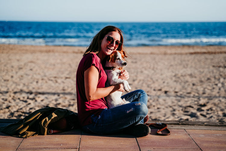 Young woman with dog sitting on beach