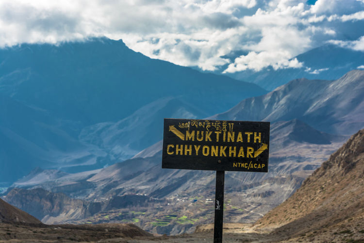 A pointer to a fork in the road in Muktinath and Chinchar, Nepal. Beauty In Nature Cloud - Sky Communication Day Environment Formation Guidance Information Information Sign Landscape Mountain Mountain Peak Mountain Range Nature No People Non-urban Scene Outdoors Scenics - Nature Sign Sky Snowcapped Mountain Text Tranquil Scene Tranquility Western Script