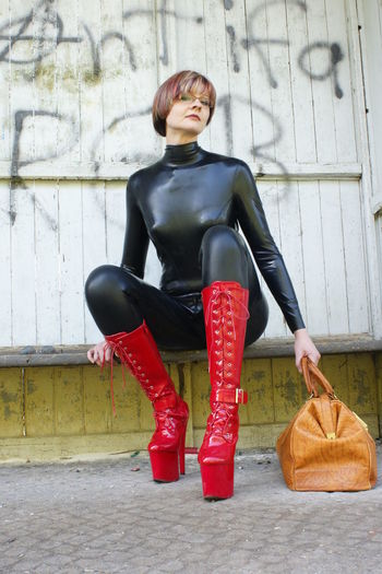 Full length of woman in latex clothing sitting against wall
